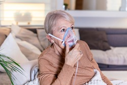 Sick elderly woman on oxygen mask inhalation, pneumonia coronavirus pandemic. ill senior woman wearing an oxygen mask and undergoing treatment. senior woman with covid 19
