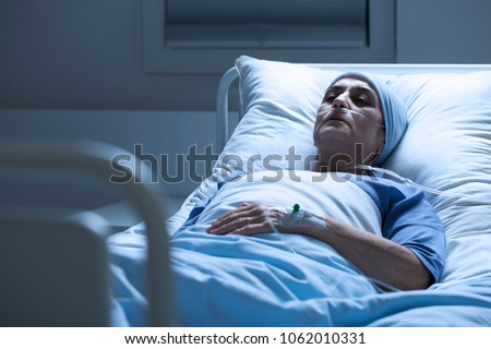 Sick, elderly woman with a headscarf and eyes closed dying alone of cancer in a hospital bed Stock foto ©