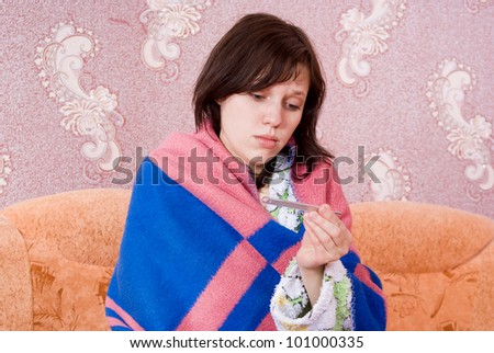 sick girl on the couch with a thermometer in her dressing gown