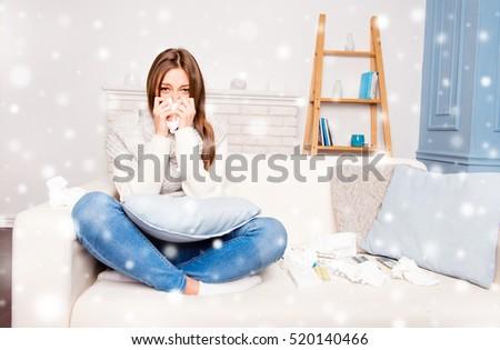 Sick  girl sneezing in tissue sitting on sofa, xmas concept