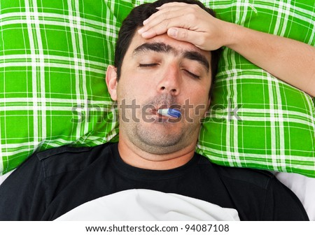 Sick hispanic man laying in bed with fever while a woman's hand touches his forehead