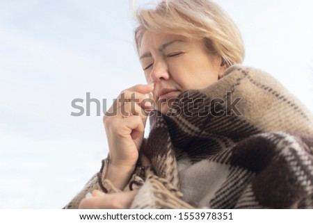 Sick ill elderly senior mature woman drips, injecting nasal drope for blocked noseRetired female with runny nose holds a medicine spray, pills in her hand. Illness, sickness. Sinusitis treatment.