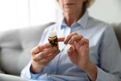 Sick ill old senior woman hold pills bottle read medicine prescription label, elderly grandma looking at medicine instructions side effects, older people pharmacy medicament concept, close up view