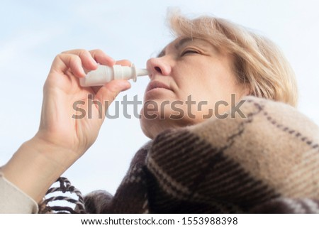 Sick ill senior mature woman drips, injecting nasal drop for blocked nose Retired female with runny nose holds medicine spray, pills in hand. Illness, sickness. Sinusitis treatment. Cold in the head.