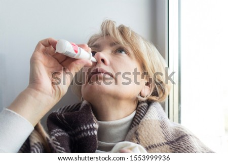 Sick ill senior mature woman drips, injecting nasal drop for blocked noseRetired female with runny nose holds medicine spray, pills in hand. Illness, sickness. Sinusitis treatment. Cold in the head.
