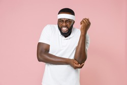 Sick injured young bearded african american fitness sports man in headband t-shirt feels bad pain spasm touching elbow arm spending time in gym isolated on pink color wall background studio portrait