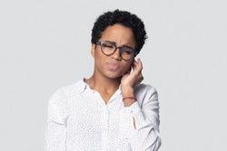 Sick irritated african american young woman suffering from strong earache head shot. Unhealthy ill ethnic frowning woman in glasses touching ear, tired of noise, isolated on gray studio background.