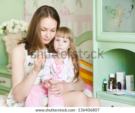 Sick kid with high fever and mother taking temperature - stock photo