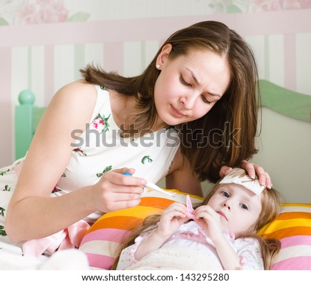 Sick kid with high fever laying in bed and mother taking temperature