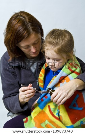 Sick litle girl on her mother knees - stock photo
