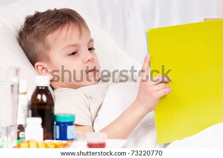 Sick little beautiful boy with book in the bed