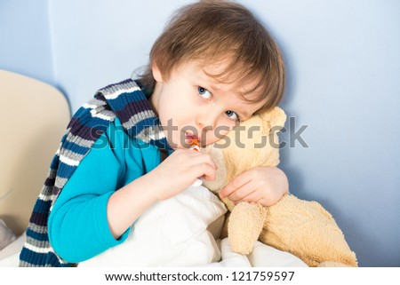 Sick little boy checking his body temperature and holding teddy bear