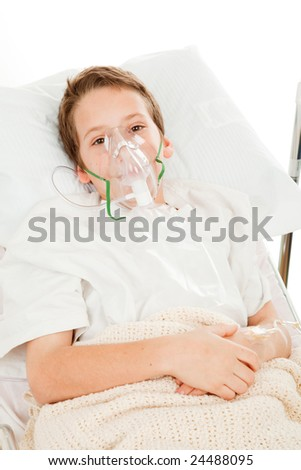 Sick little boy in the hospital breathing with an oxygen mask.