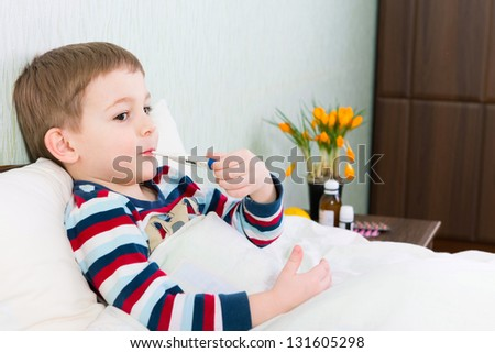 Sick little boy lying in bed with thermometer in mouth