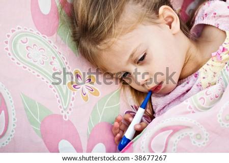 Sick little girl is having her temperature taken.