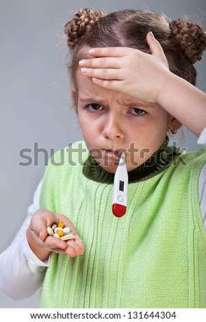 Sick little girl with the flu - holding pills and thermometer
