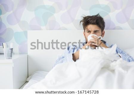 Sick man having coffee in bed - stock photo