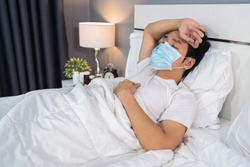 sick man in medical mask is headache and suffering from virus disease and fever in bed, coronavirus (covid-19) pandemic concept.