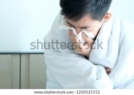 Sick man is flu, using a paper napkin and he have a runny nose. And he was covered in warm cloth.Health concept #1250525152
