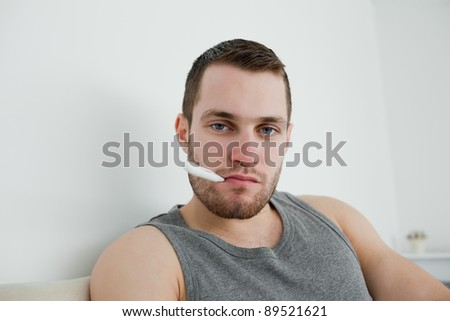 Sick man posing with thermometer in his bedroom