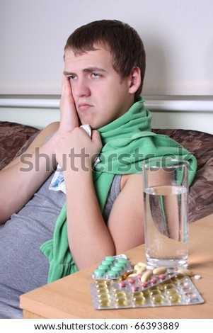 sick man sitting with tablets ans glass of water