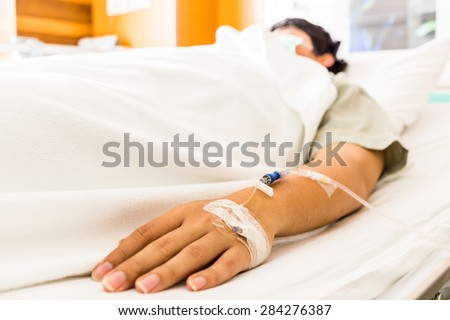 Sick man sleeping on bed at hospital