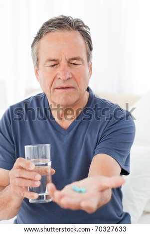 Sick man taking his pills at home - stock photo