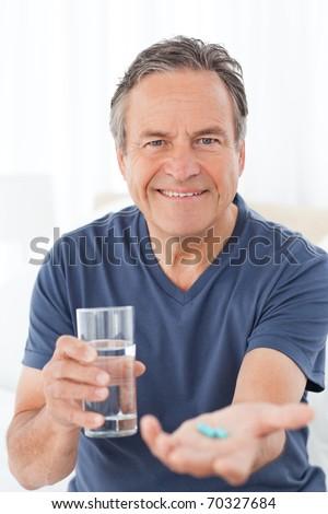 Sick man taking his pills at home