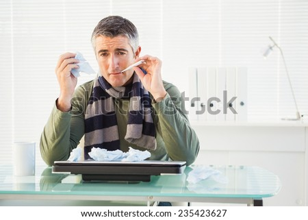 Sick man taking his temperature in his office