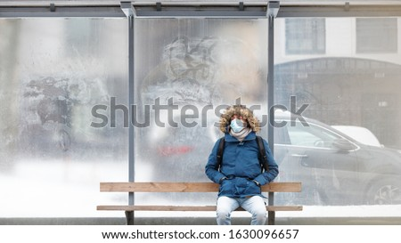 Sick man with a hood sitting alone on bench public transport, wearing protective facial mask against transmissible infectious diseases and as protection against the flu or coronavirus in public place