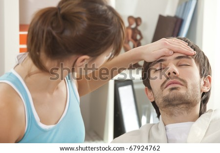 sick man with fever in bed - woman holding her hand on forehead