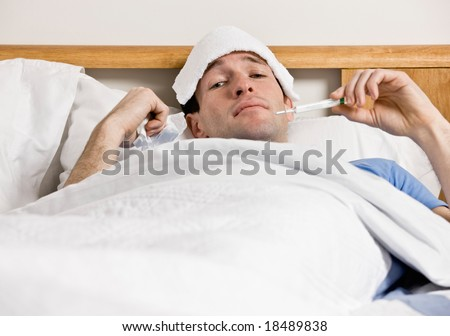 Sick man with fever laying in bed taking temperature with thermometer