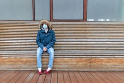Sick man with hood sitting alone on bench, wearing facial mask against transmissible infectious diseases, covid-19. Empty city from people due to coronavirus pandemic. Life in isolation and quarantine