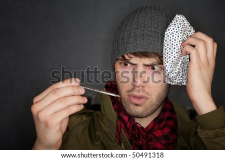 Sick man with thermometer and ice pack on head