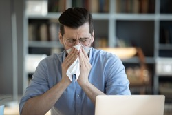 Sick millennial unhappy businessman wiping runny nose with handkerchief, suffering from seasonal allergic reaction or sneezing, caught cold feeling first flu symptoms sitting alone at workplace.