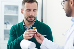 Sick patient taking pill-bottle with medication or vitamins from doctor hands