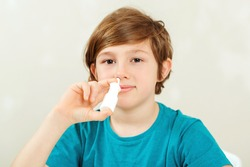 Sick school boy with runny nose using nasal medicine spray. Nasal allergy. Kid with ill disease treatment season. Allergic kid, flu season. Boy has a virus, runny nose and headache.