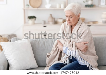 Sick senior lady sitting on couch covered with blanket, freezing shivering due to high temperature, suffering from coronavirus at home Foto stock ©