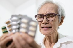 Sick senior woman holding medicine pills or capsules,sad female elderly showing a lot of drugs,treatment,medication to reduce pain,bored,afraid of taking medicine,asian old people is tired of illness