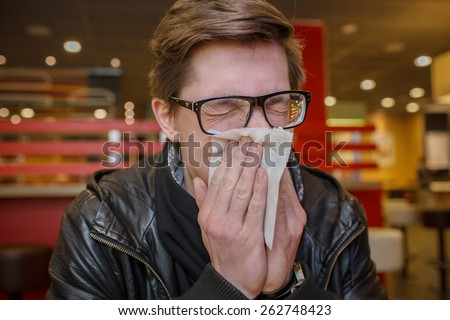 sick student blowing his nose into a tissue.
