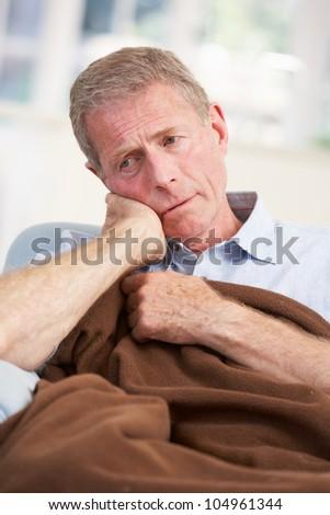 Sick, unhappy older man at home
