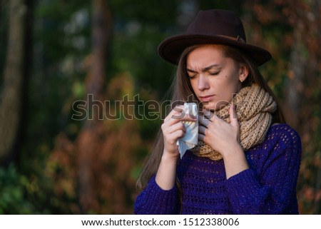 Sick unhappy woman in knitted clothes caught a cold in the fall and uses a paper napkin during sore throat outdoors. Seasonal colds and infections. Autumn cold and flu  #1512338006