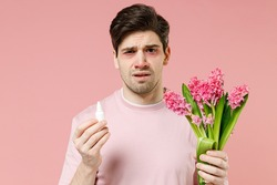 Sick unhealthy ill allergic man has red eyes runny stuffy sore nose suffer from allergy symptoms hay fever hold blooming flower plant uses nasal drops isolated on pastel pink color background studio