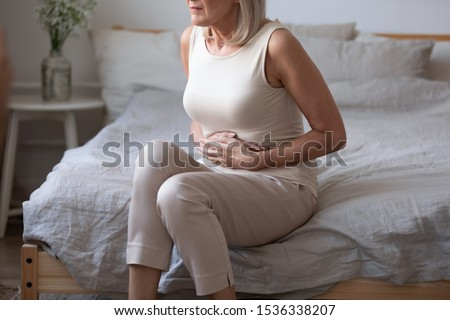 Sick upset middle aged lady hold belly suffer from abdomen ache concept, mature old adult woman feel morning pain hurt in stomach abdominal gastritis pancreatitis diarrhea problem symptom sit on bed