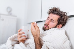 sick wasted man lying in bed wearing pajama suffering cold and winter flu virus having medicine tablets in health care concept Drinking pills with glass of water