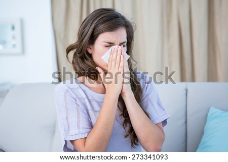 Sick woman blowing her nose at home in the living room Stock photo ©