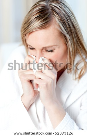 Sick woman blowing sitting on a sofa