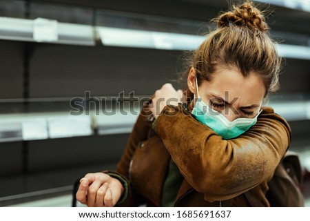Sick woman buying in supermarket and coughing into elbow during COVID-19 pandemic.