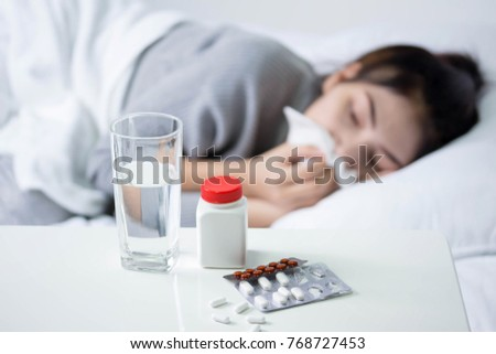 Sick woman covered with a blanket lying in bed with high fever and a flu, resting. Teapot, pills and lemon on the table