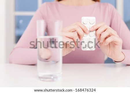 Sick woman. Cropped image of woman holding medicines while sitting at the table